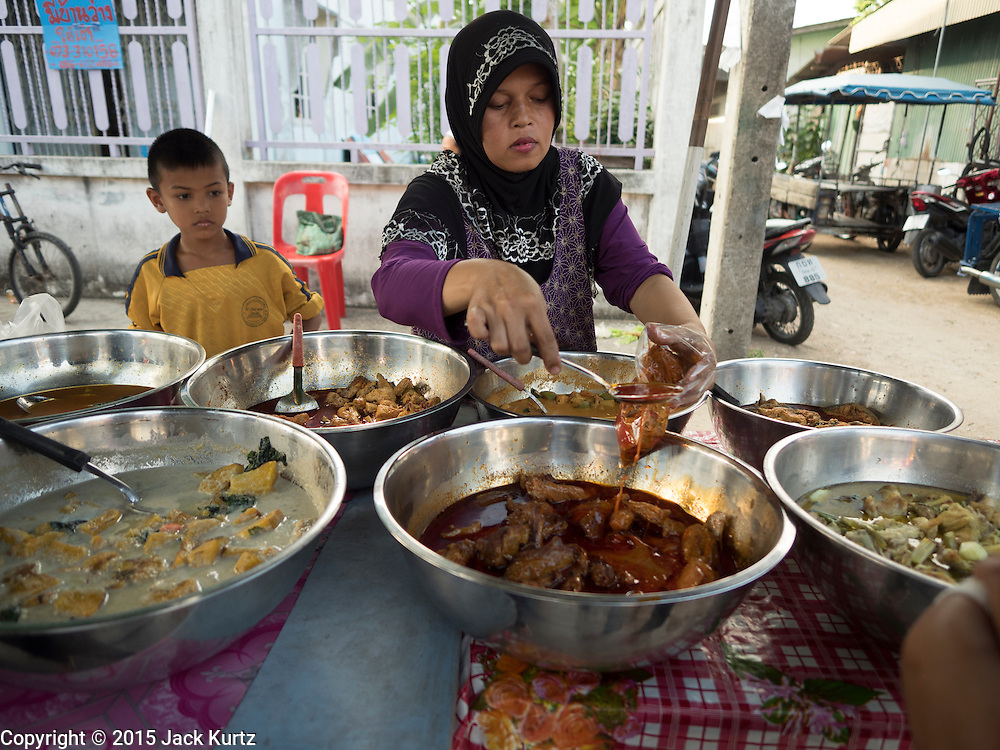 18 JUNE 2015 - PATTANI, PATTANI, THAILAND:   A woman sells curries at the Pattani Ramadan Bazaar, a sprawling street food market that is only open during Ramadan. People come to the street food market late in the day to buy meals for the evening Iftar meal, which breaks the day long fast. Ramadan is the ninth month of the Islamic calendar, and is observed by Muslims worldwide as a month of fasting to commemorate the first revelation of the Quran to Muhammad according to Islamic belief. This annual observance is regarded as one of the Five Pillars of Islam. Islam is the second largest religion in Thailand. Pattani, along with Narathiwat and Yala provinces, all on the Malaysian border, have a Muslim majority.       PHOTO BY JACK KURTZ