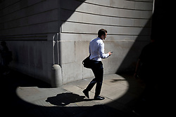© Licensed to London News Pictures. 25/06/2018. London, UK. A city worker passes through a circle of sunlight formed at the corner of the Bank of England as high temperatures remain in most of the UK. Photo credit: Peter Macdiarmid/LNP