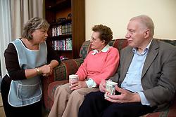 Carer talking older couple at home,