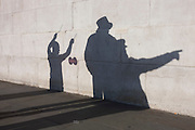 """Two buskers are questioned by a police officer, their shadows played on a stone wall in Trafalgar Square.<br /> <br /> The diabolo (commonly misspelled as diablo; formerly also known as """"the devil on two sticks"""") is a juggling prop consisting of a spool which is whirled and tossed on a string tied to two sticks held one in each hand. A huge variety of tricks are possible using the sticks, string, and various body parts."""