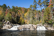See Upper Linville Falls with autumn foliage colors vibrant in mid October. Walk Erwins View Trail (1.8 miles round trip) to see Upper Linville Falls plus the more-impressive Lower Falls, in Burke County, Pisgah National Forest, North Carolina, USA. Linville Falls drop 90 feet in multi-level cascades, viewable from several overlooks along two trails starting from Linville Falls Visitors Center, run by the National Park Service. Directions: Turn eastwards at Mile Post 316.3 of the Blue Ridge Parkway (north of where US 221 crosses the Parkway and south of where NC 181 crosses). Linville River begins at Grandfather Mountain and enters the 12-mile Linville Gorge at Linville Falls. Linville Gorge, near the town of Linville Falls (66 miles north of Asheville), is the deepest and one of the most rugged and scenic gorges in the Eastern USA (qualifying for the nickname Grand Canyon of the East, along with more than a dozen chasms likewise tagged in other Eastern states). It is protected by Linville Gorge Wilderness Area, within Pisgah National Forest. Spared by its rugged terrain from clear-cutting in the early 1900s, Linville Gorge has some of the best remnant stands of uncut, old-growth forest in the southern Appalachians. This is one of the few places where the Rosebay, Catawba, and Carolina rhododendron grow side by side.