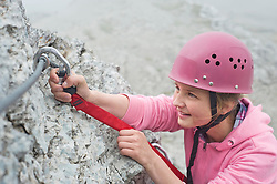 Teenage girl climbing attaching carabiner to rope