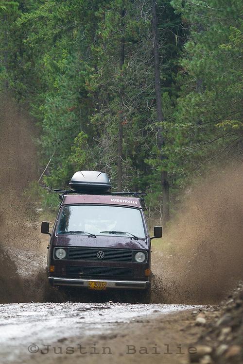 VW van driving really fast through mud puddles near Mt Rainier, WA.