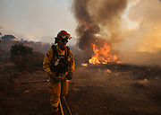 A fighter watch a wildfire near Placenta Canyon Road in Santa Clarita, Calif., Sunday, July 24, 2016.(AP Photo/Ringo H.W. Chiu)