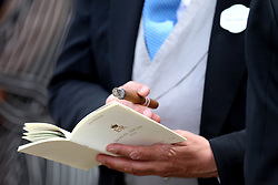 A racegoer looks at a programme during day five of Royal Ascot at Ascot Racecourse.