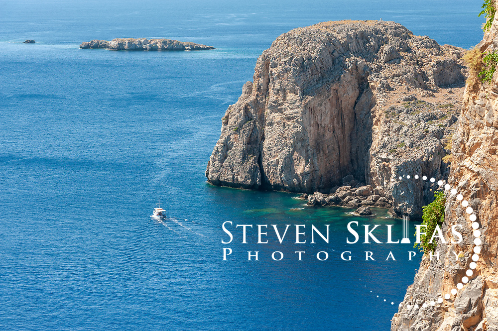 Rhodes. Greece. View of a boats sailing the blue waters below the acropolis of Lindos.