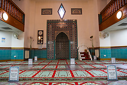 © Licensed to London News Pictures. 06/07/2020. London, UK. 'PRAY HERE. PLACE YOUR MAT IN THIS SPACE' signs are places 2 meters apart inside the Mosque for the worshippers. Wightman Road Mosque, also known as London Islamic Cultural Society and Mosque, in north London, prepares to open after the COVID-19 lockdown, by placing a number of measures required by law for worshippers. The government announced that gatherings of more than 30 worshippers are allowed for acts of communal worship in churches, synagogues, mosques, temples and other places of worship. All worshippers attending Mosques will have to wear face coverings and bring their own prayer mat, Quran, and a reusable shoe bag. Photo credit: Dinendra Haria/LNP