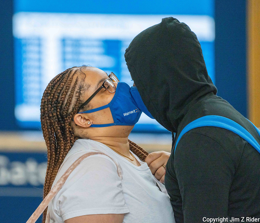 A couple kisses through their masks as they wait to board an Amtrack train Friday at 30th St. Station in Philadelphia, Pennsylvania.