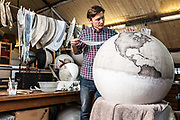 Peter Bellerby of Bellerby and Co. Globemakers adds detail to a large globe, Hackney, London, UK