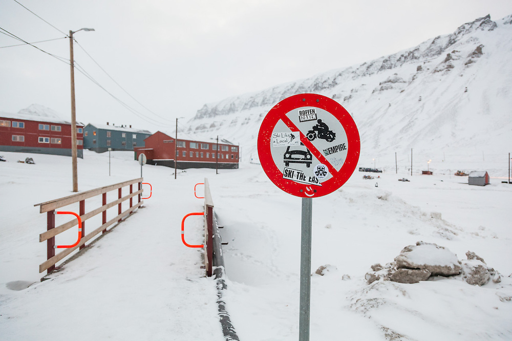 A no motorized vehicles sign covered with ski stickers on a ski trail in Longyearbyen, Svalbard.