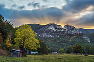 The sun begins to rise as the rays peak above Seneca Rocks in West Virginia overlooking a small farm in the beginnings of autumn.