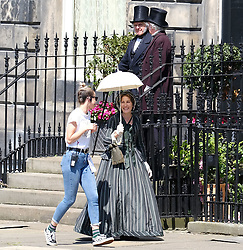 """Moray Place in Edinburgh's Georgian old town was turned into 19th century London for Julian Fellowes' new ITV show """"Belgravia"""".<br /> <br /> Pictured: Tamsin Greig (striped dress) takes up position and enjoys some sun during takes.<br /> <br /> Alex Todd 