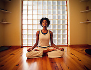 A woman sits on her nice wood floors for her morning yoga