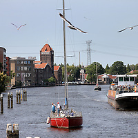 Nederland, Zaandam , 5 juli 2013.<br /> Wandeling door de binnenstad van Zaandam.<br /> Starten bij De Werf aan de Oostzijde. Daarvandaan kun je lopen op een soort boulevard tussen de flats en het water. De eerste stop is De Fabriek, filmhuis en eetcafé met terras aan de Zaan met uitzicht op de sluis. Daarna de sluis zelf.<br /> Dan langs het winkelgebied richting de Koekfabriek: Het oude Verkade pand dat is verbouwd en waar nu de bieb en sportschool en restaurant etc. in zitten.<br /> (Dat is aan de overkant van het startpunt) en misschien nog de Zwaardemaker meepakken aan de Oostzijde. Dat is een oud pakhuis die Rochdale enige jaren geleden heeft verbouwt tot appartementen met een stukje Nieuwbouw.<br /> Ook doen: het Russische buurtje vlakbij de Zaan. Dit jaar staat Rusland in de schijnwerpers en Zaandam heeft een speciale band met Rusland, vanwege het Czaar Peterhuisje en de Russische buurt. <br /> Op de foto: De Zaan bij Zaandam<br /> Foto:Jean-Pierre Jans