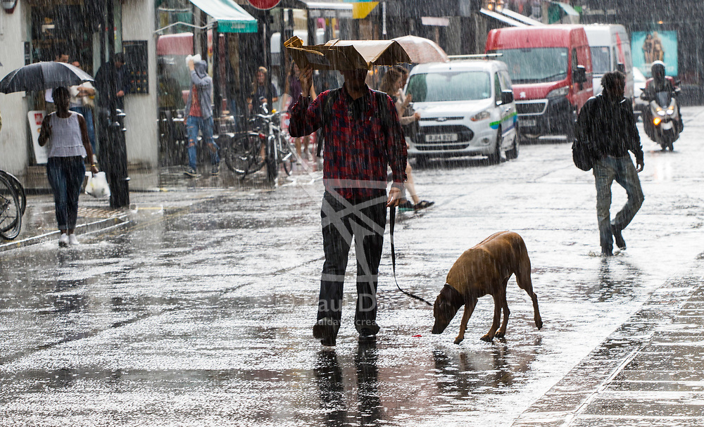 Soho, London, June 2nd 2017. A man with a dog uses a collapsed cardboard carton for shelter as one of the thunderstorms predicted by the Met Office passes over Old Compton Street in Soho, London.