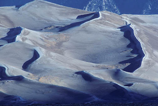 Great Sand Dunes National Monument, Morning light lifts shadows from frost covered dunes. Early winter. Colorado.