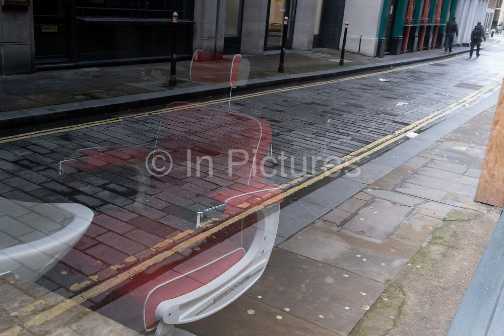 An empty chair remains empty in the window of a closed business on the cobbled former Roman-era Watling Street, during the third lockdown of the Coronavirus pandemic, in the City of London, the capitals financial district, aka The Square Mile, on 2nd February 2021, in London, England.