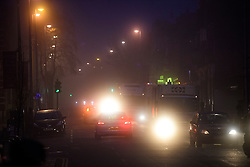 © Licensed to London News Pictures. 22/12/2016. London, UK. Traffic makes it's way along Acton high Street in West London in thick fog on a cold winter morning. Temperatures over the upcoming Christmas period are expected to be unusually warm. Photo credit: Ben Cawthra/LNP