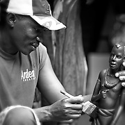 """""""Artist Pride""""                                                     Tanzania<br />  I came across this craftsman in Arusha and was immediately captured by his passion for his work.  If you look closely at the carving, you'll see similarities in both the carving and the wood carver."""