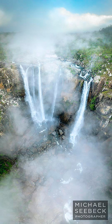 An aerial photograph of a spectacular waterfall enshrouded in early morning mist, in the wet tropics wilderness of Far North Queensland.<br /> <br /> Limited Edition of 125.<br /> <br /> Available as a Fine Art Print, acrylic face-mounted print or an alugraph.