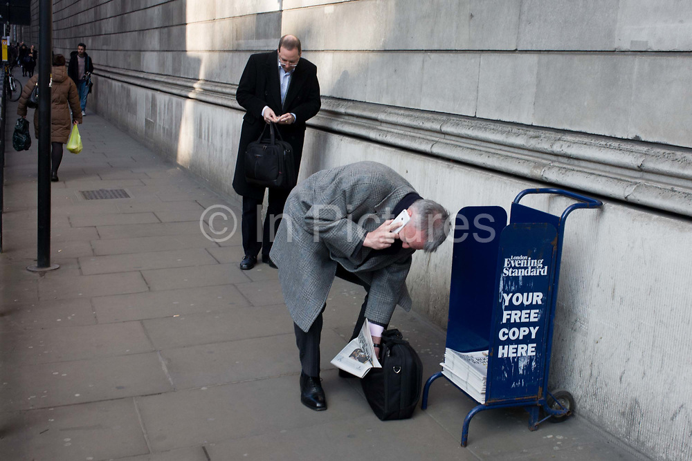 While holding a conversation on his smartphone, a stooping gent struggles to slide a free copy of the Evening Standard newspaper into his briefcase, beneath the high walls of the Bank of England in the City of London. Bending down to stuff the newspaper into his bag, the businessman awkwardly maintains his chat on the phone. The man behind texts on his own phone too. Above them and in the distance are the walls of the Bank - known as the Old Lady of Threadneedle Street - the monetary regulator of Britain's economy.