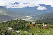 Landscape view across rural Bhutan, with traditional farms and river, Punakha..Bhutan the country that prides itself on the development of 'Gross National Happiness' rather than GNP. This attitude pervades education, government, proclamations by royalty and politicians alike, and in the daily life of Bhutanese people. Strong adherence and respect for a royal family and Buddhism, mean the people generally follow what they are told and taught. There are of course contradictions between the modern and tradional world more often seen in urban rather than rural contexts. Phallic images of huge penises adorn the traditional homes, surrounded by animal spirits; Gross National Penis. Slow development, and fending off the modern world, television only introduced ten years ago, the lack of intrusive tourism, as tourists need to pay a daily minimum entry of $250, ecotourism for the rich, leaves a relatively unworldly populace, but with very high literacy, good health service and payments to peasants to not kill wild animals, or misuse forest, enables sustainable development and protects the country's natural heritage. Whilst various hydro-electric schemes, cash crops including apples, pull in import revenue, and Bhutan is helped with aid from the international community. Its population is only a meagre 700,000. Indian and Nepalese workers carry out the menial road and construction work.