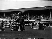 """05/08/1960<br /> 05/08/1960<br /> 05 August 1960<br /> R.D.S Horse Show Dublin (Friday). Aga Khan Trophy. Lieut-Col. Carlos Delia (Argentina) on """"Huipil"""", clearing the last jump in the Aga Khan  Trophy Event at the Dublin Horse Show."""