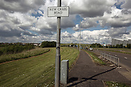 'Untitled, 2014' from the project 'The Fall and Rise of Ravenscraig' by photographer Colin McPherson.<br /> <br /> The photograph shows New Craig Road, the so-called 'spine road' constructed on the site of the former steelworks at Ravenscraig.<br /> <br /> This project, photographed in 2014, looks at the topography of the post-industrial landscape at Ravenscraig, the site until its closure in 1992 of the largest hot strip steel mill in western Europe. In its current state, Ravenscraig is one of the largest derelict sites in Europe measuring over 1,125 acres (4.55 km2) in size, an area equivalent to 700 football pitches or twice the size of Monaco. It is currently being developed with a mix of housing, retail and the home of South Lanarkshire College and the Ravenscraig Regional Sports Facility.