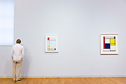 Man views Piet Mondrian oil on canvas paintings in 20th Century Gallery at Rijksmuseum, Amsterdam