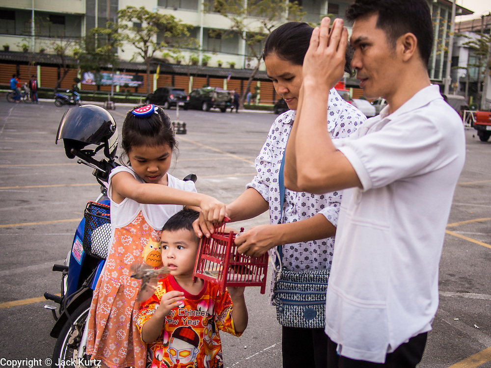 """14 FEBRUARY 2014 - BANGKOK, THAILAND:  A family releases a bird to make merit on Makha Bucha Day at Wat That Thong (also called Wat Tad Tong) in Bangkok. The aims of Makha Bucha Day are: not to commit any kind of sins, do only good and purify one's mind. It is a public holiday in Cambodia, Laos, Myanmar and Thailand. Many people go to the temple to perform merit-making activities on Makha Bucha Day. The day marks four important events in Buddhism, which happened nine months after the Enlightenment of the Buddha in northern India; 1,250 disciples came to see the Buddha that evening without being summoned, all of them were Arhantas, Enlightened Ones, and all were ordained by the Buddha himself. The Buddha gave those Arhantas the principles of Buddhism, called """"The ovadhapatimokha"""". Those principles are:  1) To cease from all evil, 2) To do what is good, 3) To cleanse one's mind. The Buddha delivered an important sermon on that day which laid down the principles of the Buddhist teachings. In Thailand, this teaching has been dubbed the """"Heart of Buddhism.""""   PHOTO BY JACK KURTZ"""