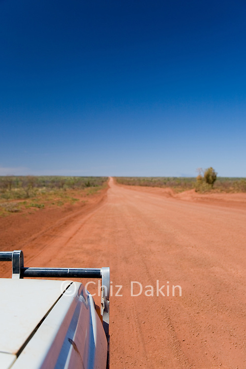The typical outback view (straight dirt road stretching for km ahead) from a 4WD vehicle, Pilbara region, Western Australia