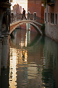 Businessman crossing a bridge in a narrow canal in Venice, Italy