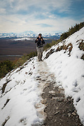 Woman hiking through snow with Mt. McKinley in the distant background, Denali National Park, Alaska