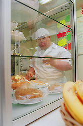 Reflection of man with Downs Syndrome wearing cook's clothes in kitchen,