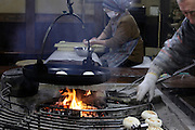 preparing Oyaki buns above an indoors open fire Nagano Japan