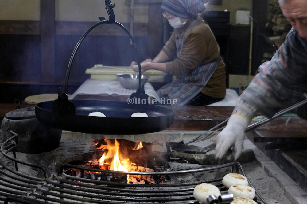 preparing Oyaki buns above an indoors open fire Nagano Japan