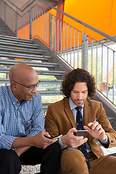 Holding cell phone talking two men steps sitting