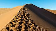 "Person climbing ""Big Daddy"" sand dune with many footprints, Sossusvlei desert, Namib-Naukluft National Park, Namibia."