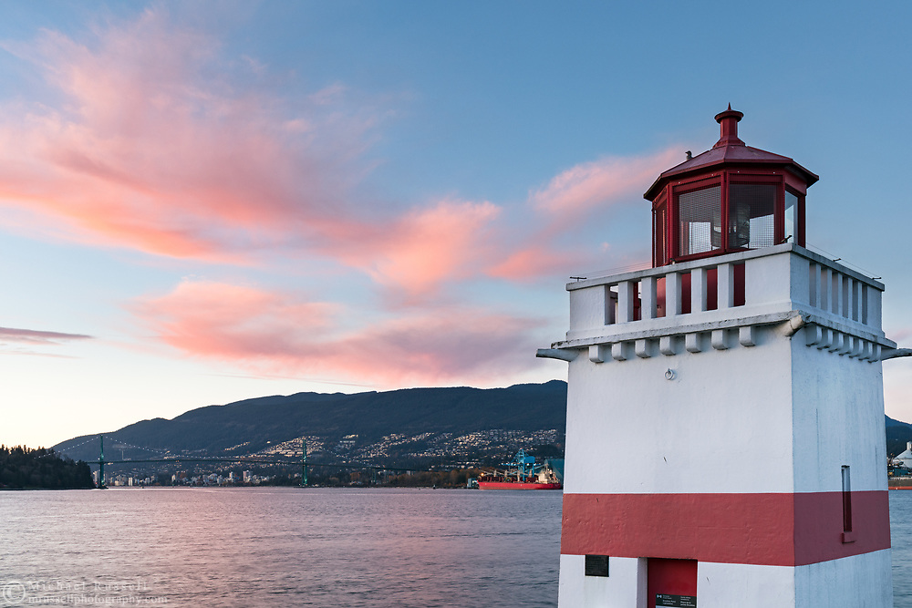 Sunset light on clouds with the Brockton Point Lighthouse (built in 1914).  Photographed from Brockton Point at Stanley Park in Vancouver, British Columbia, Canada with North Vancouver, West Vancouver, and the Lions Gate Bridge in the background.