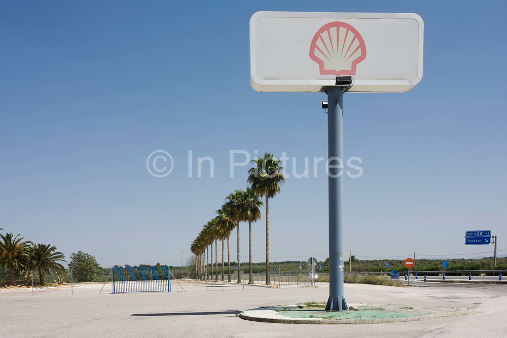 """A tall Shell sign seems to echo the palm tree landscape alongside the A 92 motorway near Paradas. On the main highway between the Andalucian cities of Granada and Seville, the corporate logo appears to be higher than the growing trees in the distance. The word """"Shell"""" first appeared in 1891 as the trademark for the kerosene that Marcus Samuel and Company shipped to the Far East. The small London business dealt originally in antiques and oriental seashells. In 1897 Samuel formed The Shell Transport and Trading Company. The first logo in 1901 was a mussel shell. In 1904 a scallop shell, or Pecten, gave a visual element to the corporate and brand name."""