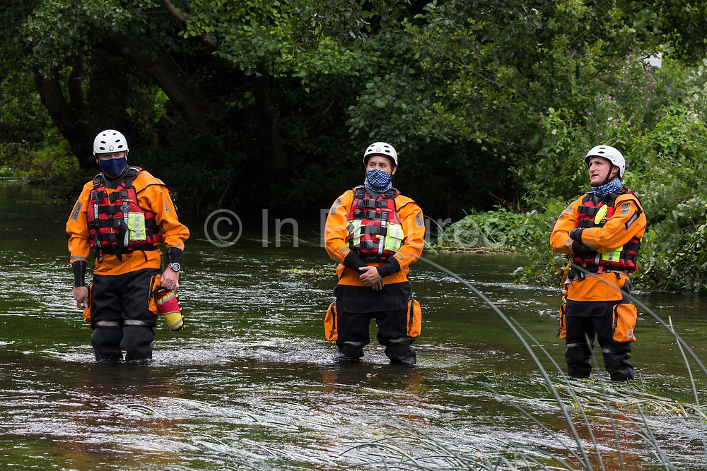 Police officers from Hampshire Police Marine Support Unit stand in the river Colne during a large policing operation to ensure that environmental activists from HS2 Rebellion did not prevent removal of an ancient alder tree for the HS2 high-speed rail link on 24th July 2020 in Denham, United Kingdom. Officers from the Metropolitan Police, Thames Valley Police, City of London Police and Hampshire Police attended as well as the National Eviction Team.