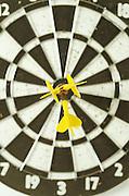 dart board with three darts at bulls eye