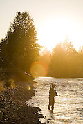 Jeremy Cram, backlit by a setting sun, casts his fly fishing line into the Yakima River near Cle Elum, Washington.