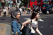 Girls out shopping on Oxford Street in London, UK. Happy and crossing the road one fo the girls is wearing a Muslim head scarf.