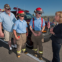 Montana Democratic Congressional candidate Franke Wilmer talks with firemen at the Butte 4th of July parade.