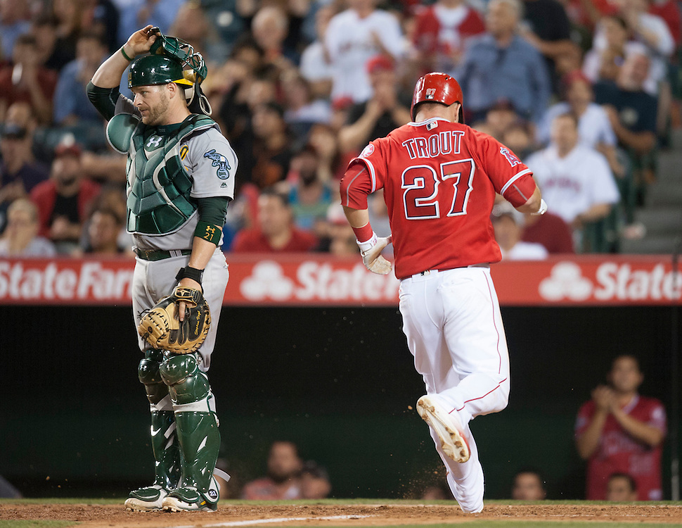 The Angels' Mike Trout scores past Athletics' catcher Stephen Vogt in the fourth inning during the Angels' 5-4 loss to the Oakland Athletics at Angel Stadium on Thursday.<br /> <br /> ///ADDITIONAL INFO:   <br /> <br /> angels.0624kjs  ---  Photo by KEVIN SULLIVAN / Orange County Register  --  6/23/16<br /> <br /> The Los Angeles Angels take on the Oakland Athletics Thursday at Angel Stadium.<br /> <br /> <br />  6/23/16