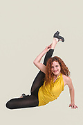 Flexibility concept red haired female model stretching out on white background