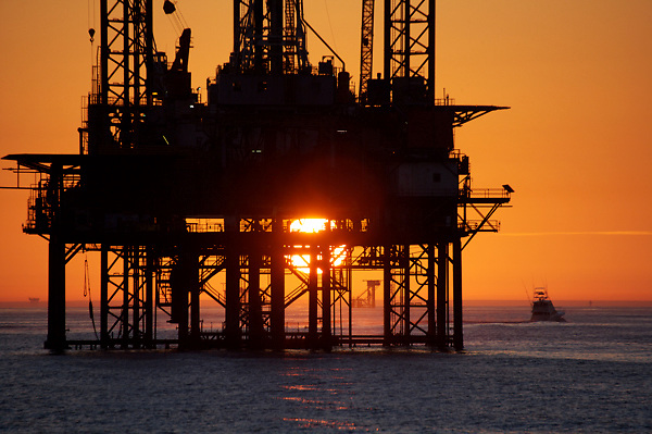 Silhouette of an offshore oil rig at sunset.