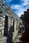 """Tourists explore a restored Inca stone corridor at Machu Picchu, a magnificent archeological site in the Cordillera Vilcabamba, Andes mountains, Peru, South America. Machu Picchu was built around 1450 AD as an estate for the Inca emperor Pachacuti (14381472). Spaniards passed in the river valley below but never discovered Machu Picchu during their conquest of the Incas 1532-1572. The outside world was unaware of the """"Lost City of the Incas"""" until revealed by American historian Hiram Bingham in 1911. Machu Picchu perches at 2430 meters elevation (7970 feet) on a well defended ridge 450 meters (1480 ft) above a loop of the Urubamba/Vilcanota River ( Sacred Valley of the Incas). UNESCO honored the Historic Sanctuary of Machu Picchu on the World Heritage List in 1983."""