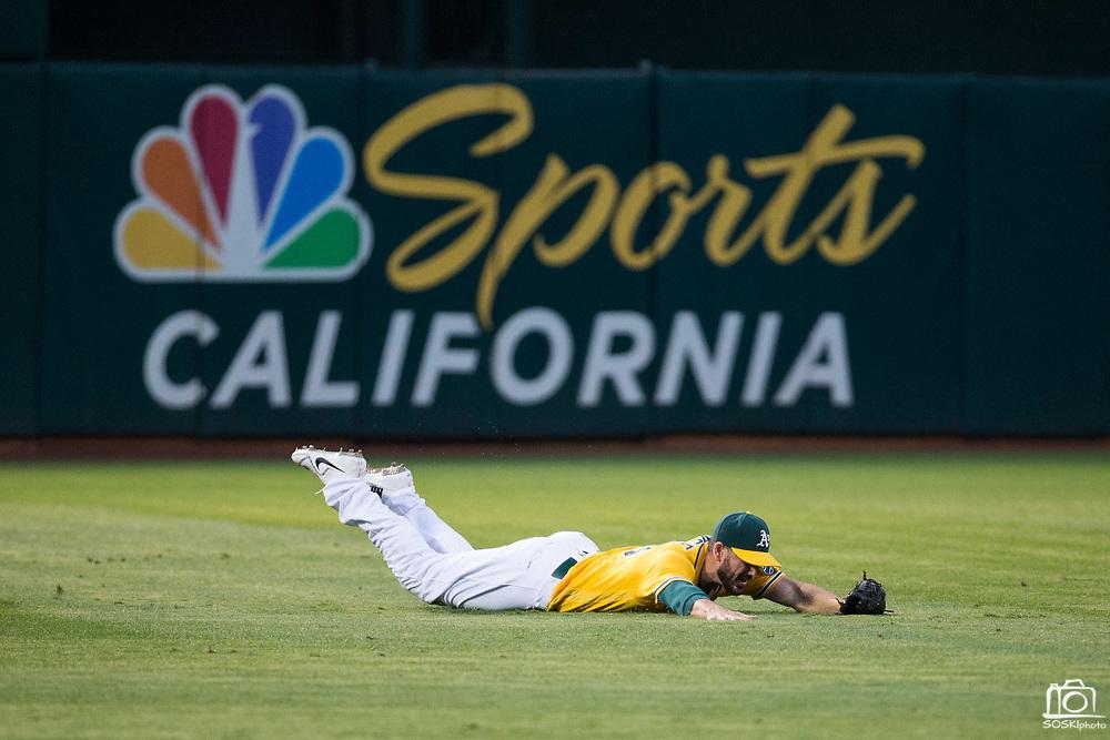 Oakland Athletics left fielder Matt Joyce (23) dives for a ball against the Los Angeles Angels at Oakland Coliseum in Oakland, California, on September 5, 2017. (Stan Olszewski/Special to S.F. Examiner)